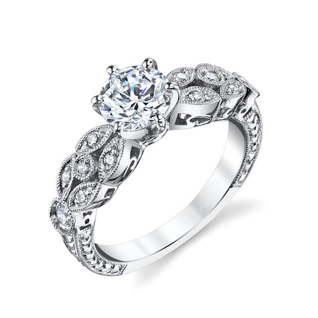 Item # E32568WE - 18kt white gold, vintage with a modern twist, diamond engagement ring. There are about 12 round brilliant cut diamonds set in the ring. The diamonds are about 0.21 ct tw, VS1-2 in clarity and G-H in color. Center stone is sold separately and in different sizes. Pictured is a 1.0 carat diamond.