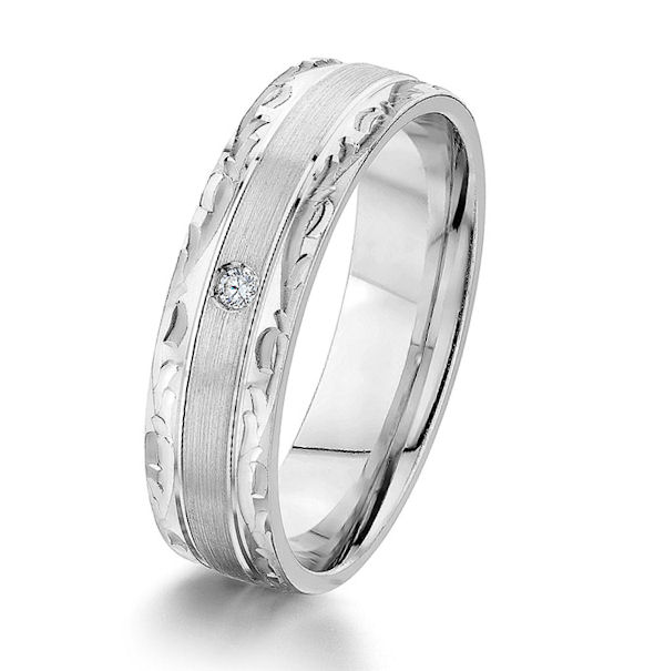 Item # G67190WE - 18kt white gold, carved, 6.0 mm wide, diamond comfort fit wedding ring. There is one round brilliant cut diamond set in the ring. The diamond is about 0.02 carats, VS1-2 in clarity and G-H in color. The center of the ring is a brushed finish and the edges have a polished design finish. The ring is 6.0 mm wide.