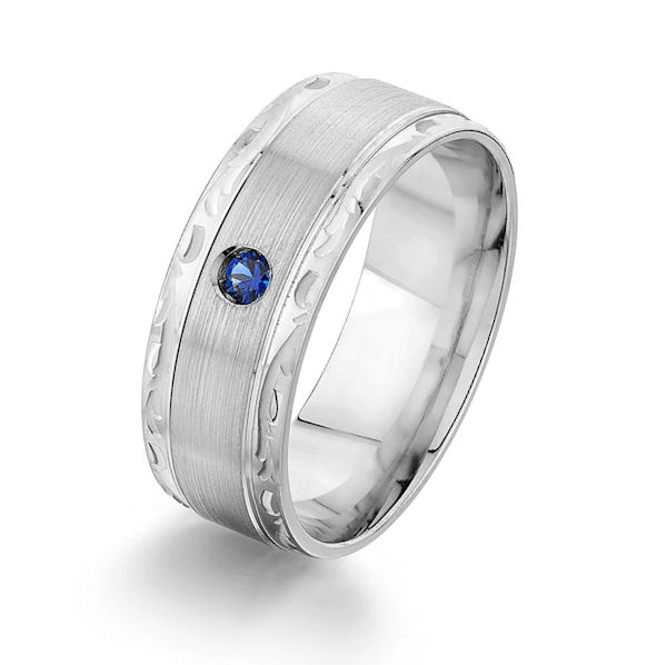 Item # GS87190WE - 18kt white gold, blue sapphire, carved, comfort fit wedding ring. There is one round brilliant cut genuine blue sapphire that measures about 2.3 mm in size set in the ring. The ring has a mix of brushed and polished finish with the edges having a carved design. The ring is 8.0 mm wide.